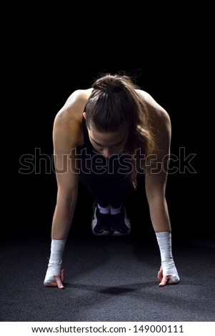 fit woman doing pushups on black background - stock photo
