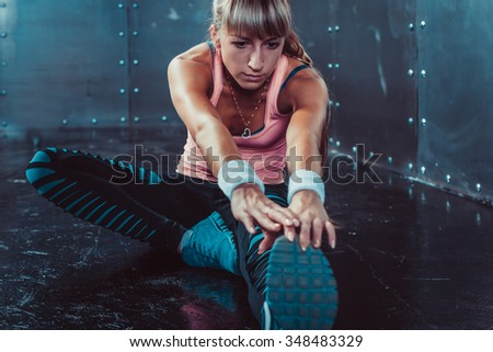 Fit woman doing stretching exercises her muscles back and legs before a training warm up at gym concept fitness, sport, lifestyle - stock photo