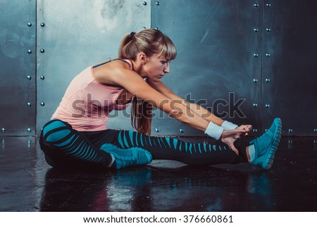 Fit woman doing stretching exercises her muscles back and legs before a training warm up at gym concept fitness, sport, lifestyle. - stock photo