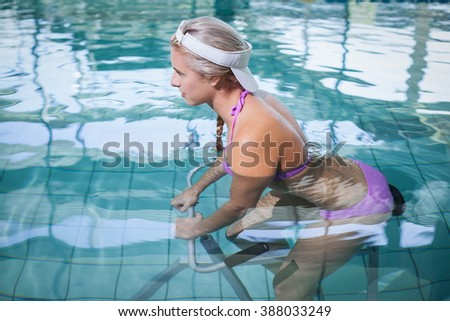 Fit woman doing underwater bike at the pool - stock photo
