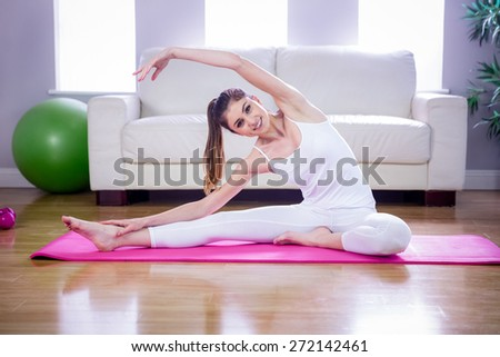 Fit woman doing yoga on mat at home in the living room - stock photo