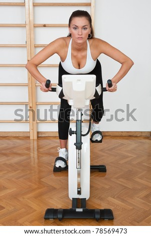 fit woman driving stationary bicycle in gym