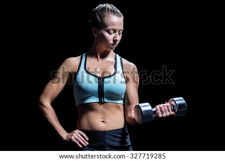 Fit woman exercising by lifting dumbbell against black background - stock photo