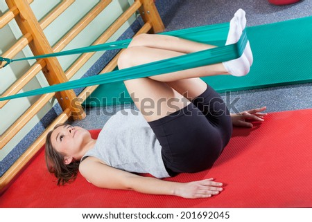 Fit woman exercising in fitness studio with elastic band - stock photo