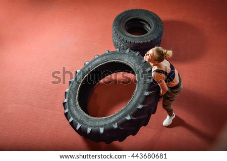 Fit woman exercising in gym using tires as equipment. - stock photo