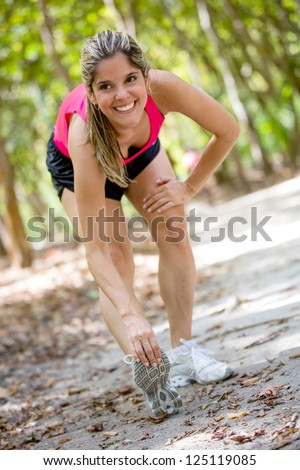 Fit woman exercising outdoors and stretching her legs - stock photo
