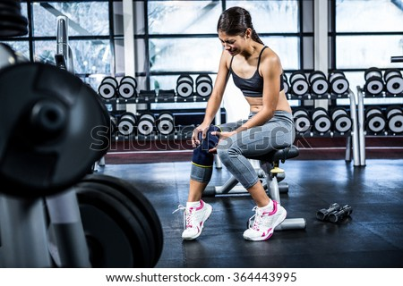 Fit woman having knees pain at gym - stock photo