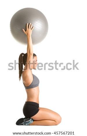 Fit woman holding a pilates ball over her head, isolated in white