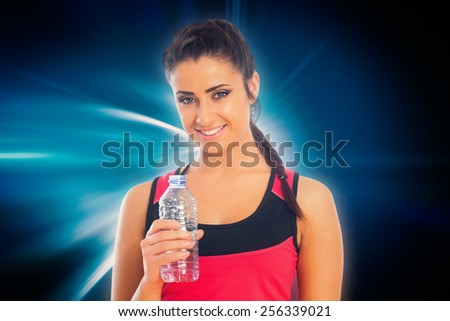 Fit woman holding water bottle against abstract background - stock photo