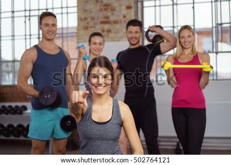 Fit woman in gray tank top pointing while friends stand behind her with exercise objects near window