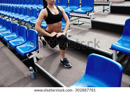 Fit woman in sportswear doing exercise for legs at stadium