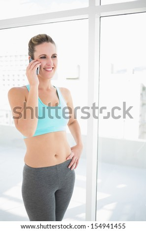 Fit woman in sportswear talking on the phone one hand on hip