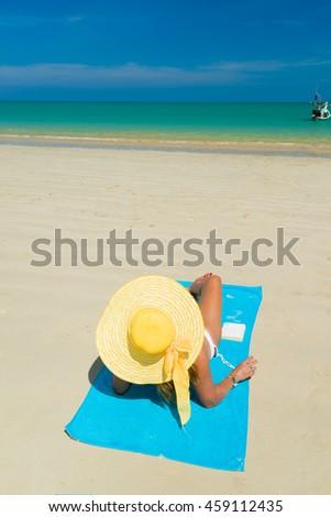 Fit woman in sun hat and bikini at the  beach - stock photo