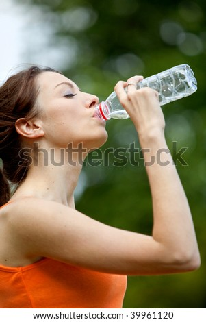 Fit woman in tracksuit drinking water outdoors - stock photo