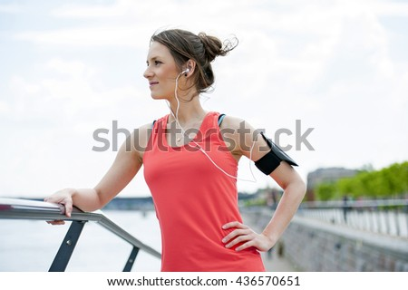 Fit woman jogger resting after run listening music. - stock photo