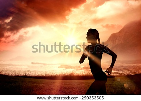 Fit woman jogging against sunrise over magical sea