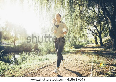 Fit woman jogging in park surrounded by trees - stock photo