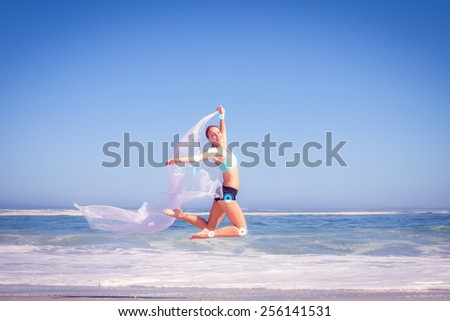 Fit woman jumping gracefully on the beach with scarf against fitness interface - stock photo