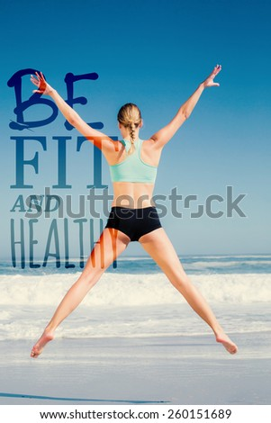 Fit woman jumping on the beach with arms out against be fit and healthy - stock photo