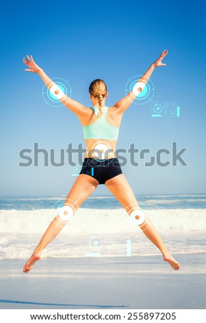 Fit woman jumping on the beach with arms out against fitness interface - stock photo