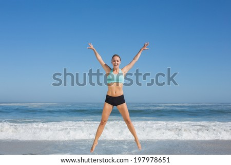 Fit woman jumping on the beach with arms out on a sunny day - stock photo