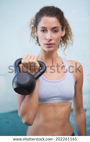 Fit woman looking at camera holding kettlebell at the gym - stock photo