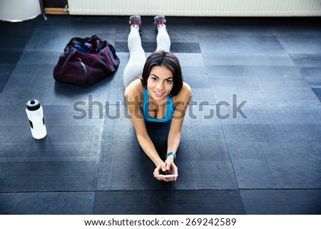 Fit woman lying on the floor at gym and looking at camera - stock photo
