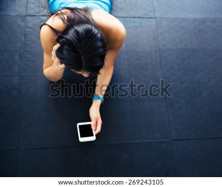 Fit woman lying on the floor with smartphone - stock photo