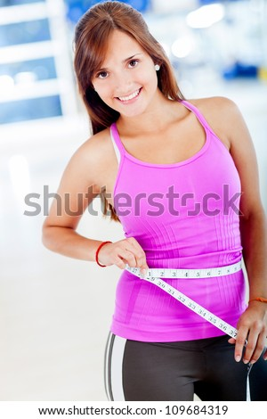 Fit woman measuring her waist and smiling - stock photo