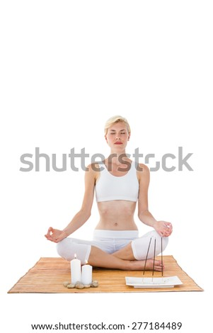 Fit woman meditating on bamboo mat on white background - stock photo