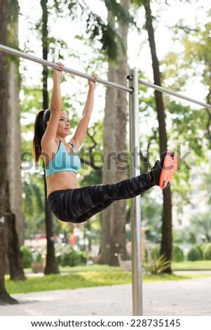 Fit woman raising her straight legs hanging on gym bar  - stock photo