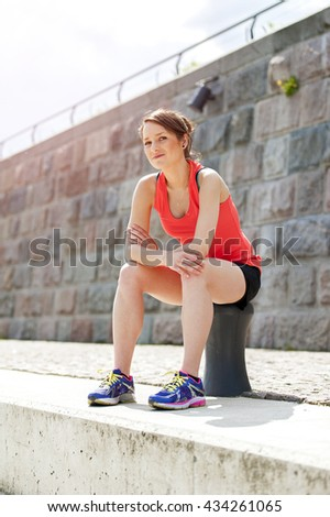 Fit woman resting after run by the river. Jogger.
