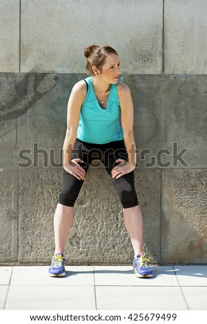Fit woman resting after run in the city. Jogger. - stock photo