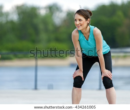 Fit woman resting after run in the park. Jogger. - stock photo