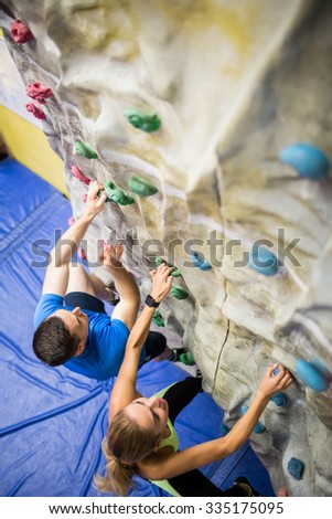 Fit woman rock climbing indoors in the gym - stock photo