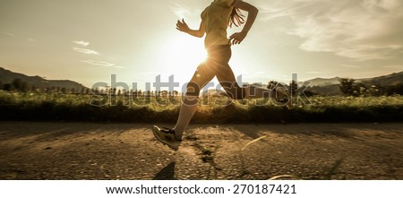 Fit woman running fast, training in bright sunshine - stock photo