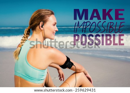 Fit woman sitting on the beach taking a break smiling against make impossible possible - stock photo