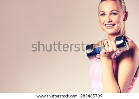 Fit woman smiling at camera and holding dumbbell to her shoulder. Image with copyspace for text - stock photo