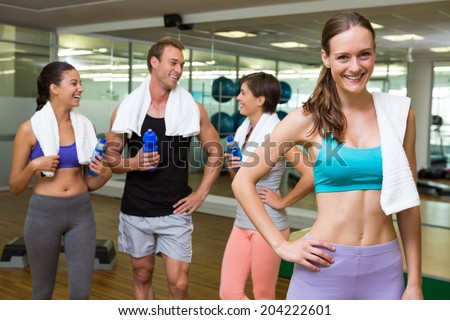 Fit woman smiling at camera in busy fitness studio at the gym - stock photo