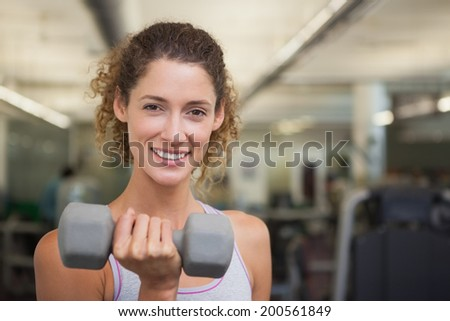 Fit woman smiling at camera lifting dumbbell at the gym