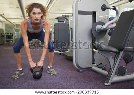 Fit woman squatting with kettlebell at the gym - stock photo