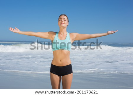Fit woman standing on the beach with arms out on a sunny day - stock photo