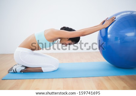 Fit woman stretching her body using a fitness ball sitting on exercise mat - stock photo