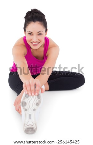 Fit woman stretching her leg on white background - stock photo