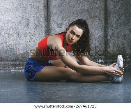 Fit woman stretching her leg to warm up - stock photo