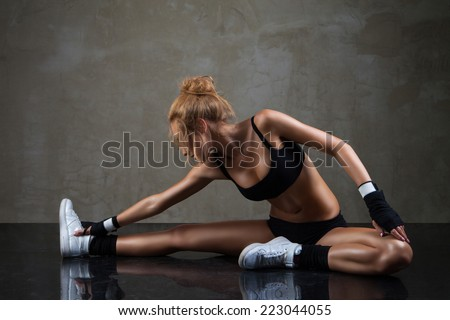 Fit woman stretching her leg to warm up over dark grey background - stock photo