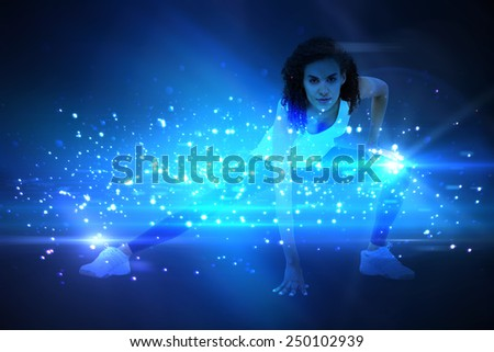 Fit woman stretching her legs against black background with spark - stock photo