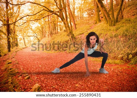 Fit woman stretching her legs against peaceful autumn scene in forest - stock photo