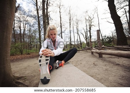 Fit woman stretching her legs before a run. Caucasian female model exercising in park. - stock photo
