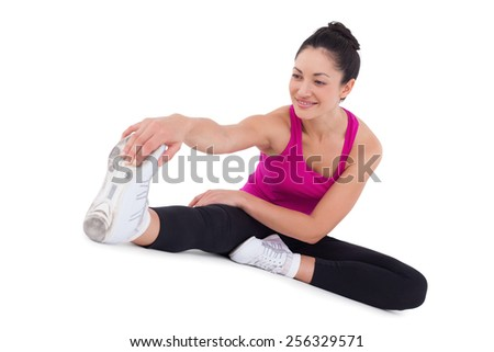 Fit woman stretching her legs on white background - stock photo